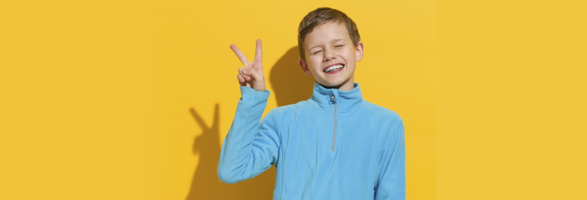 Blind child making the peace sign