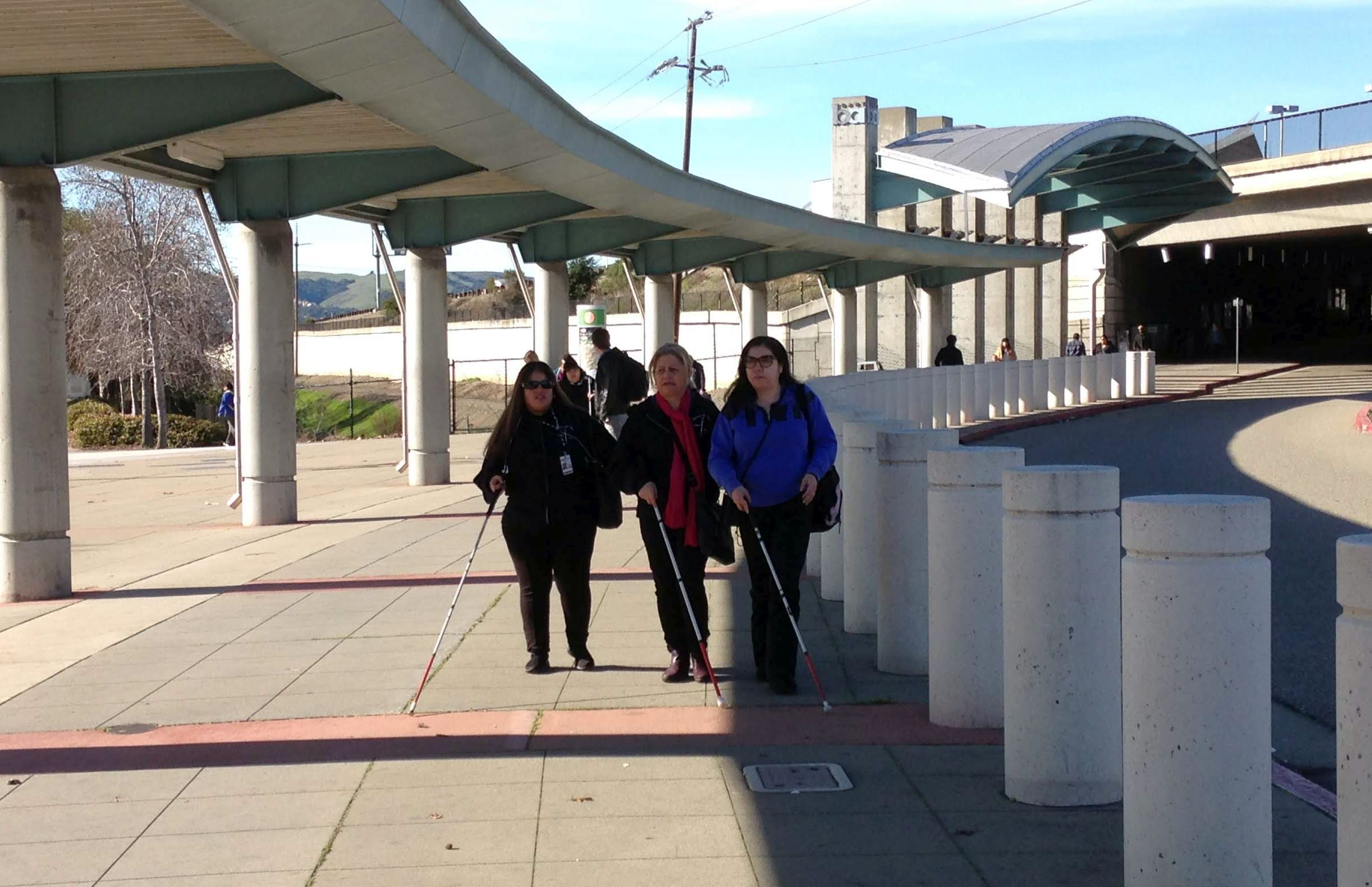 Women who are blind using white canes to travel on a BART platform.