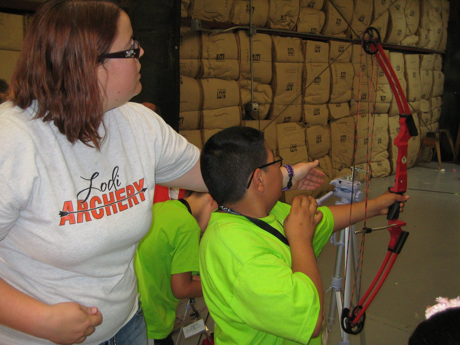 A woman shows a young boy who is visually impaired how to hold a bow.