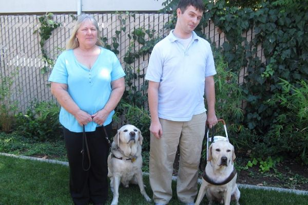 Community Center for the Blind and Visually Impaired Independent Living Skills Instructor Laurie and Adaptive Technology Instructor Hy with Guide Dogs Georgio and Fleetwood.