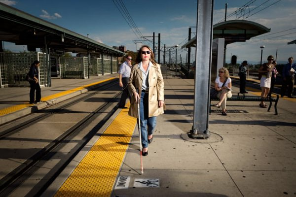 Woman who is blind using a white cane to travel on a lightrail platform.